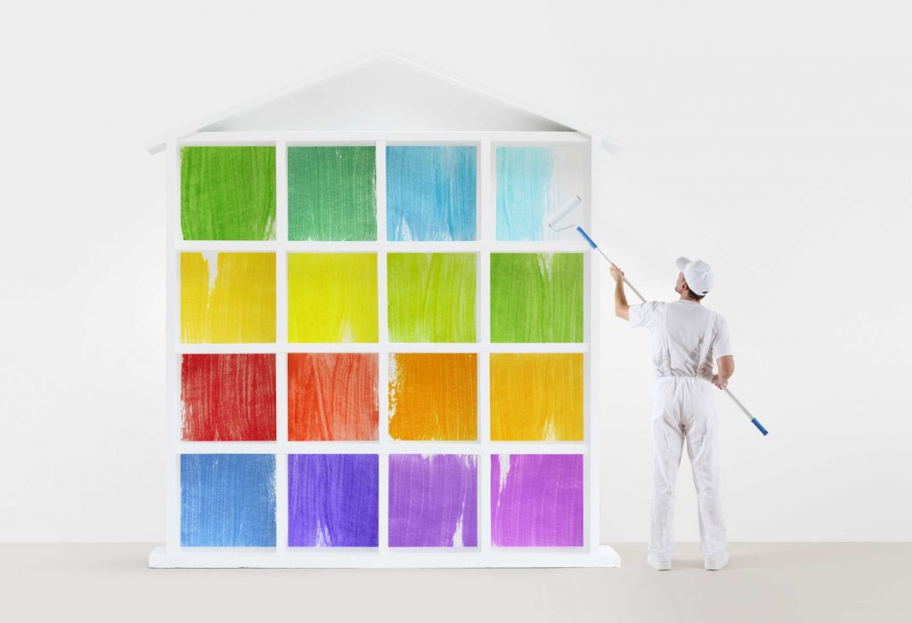 home service concept. painter man with paint roller, painting a colors house model isolated on the blank wall background
